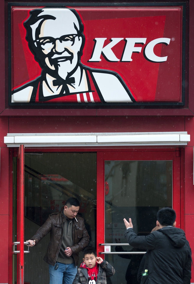 A Chinese man and a child exit a KFC restaurant in Beijing Monday, Feb. 25, 2013. KFC launched a campaign Monday to rebuild its battered brand in China, promising tighter quality control after a scandal over misuse of drugs by its poultry suppliers. (AP Photo/Andy Wong)