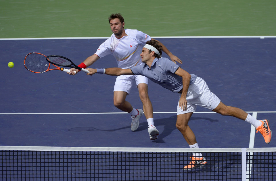 Photo - Roger Federer, of Switzerland, right, stretches for the ball as doubles partner Stanislas Wawrinka, of Switzerland, looks on during a match at the BNP Paribas Open tennis tournament against Rohan Bopanna, of India, and Aisam-Ul-Haq Qureshi, of Pakistan,  Friday, March 7, 2014 in Indian Wells, Calif. (AP Photo/Mark J. Terrill)