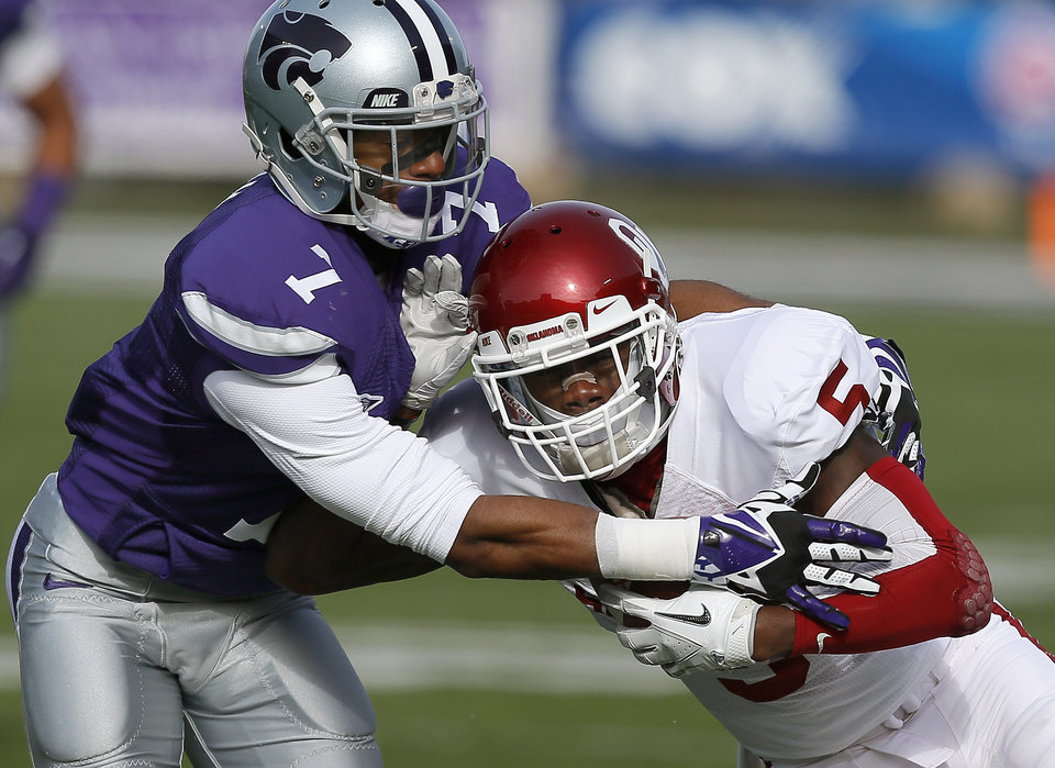 Oklahoma's Durron Neal (5) fights of Kansas State 's Kip Daily (7) during an NCAA college football game between the Oklahoma Sooners and the Kansas State University Wildcats at Bill Snyder Family Stadium in Manhattan, Kan., Saturday, Nov. 23, 2013. Oklahoma won 41-31. Photo by Bryan Terry, The Oklahoman