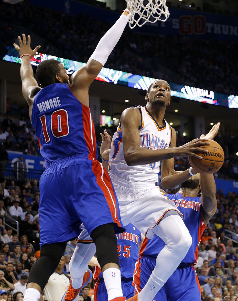 Photo - Oklahoma City's Kevin Durant (35) drives past Detroit's Greg Monroe (10) during the NBA basketball game between the Oklahoma City Thuder and the Detroit Pistons at Chesapeake Energy Arena in Oklahoma City, Okla. on Wednesday, April 16, 2014.  Photo by Chris Landsberger, The Oklahoman