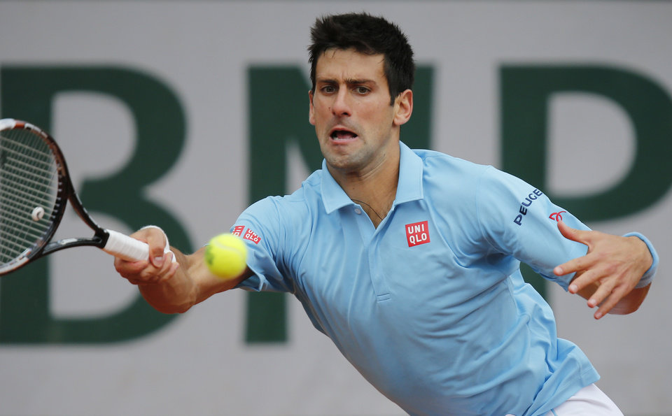 Photo - Serbia's Novak Djokovic returns the ball during the third round match of the French Open tennis tournament against Croatia's Marin Cilic at the Roland Garros stadium, in Paris, France, Friday, May 30, 2014.  (AP Photo/David Vincent)