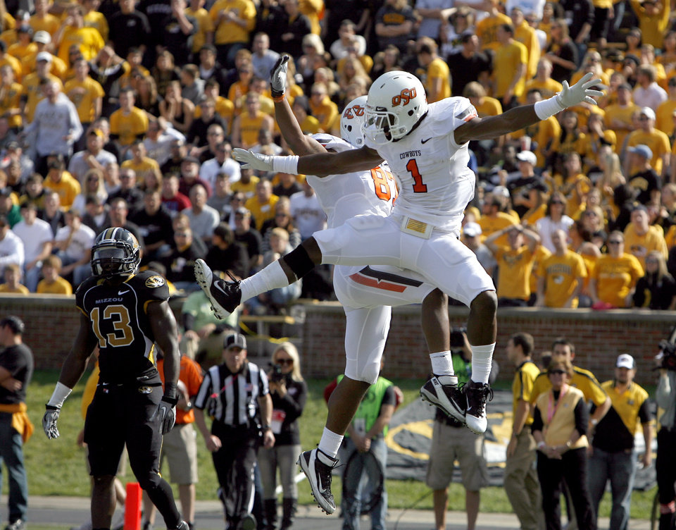 Photo - Oklahoma State's Joseph Randle (1) and Tracy Moore (87) celebrate in front of Missouri's Kenji Jackson (13) during a college football game between the Oklahoma State University Cowboys (OSU) and the University of Missouri Tigers (Mizzou) at Faurot Field in Columbia, Mo., Saturday, Oct. 22, 2011. Photo by Sarah Phipps, The Oklahoman
