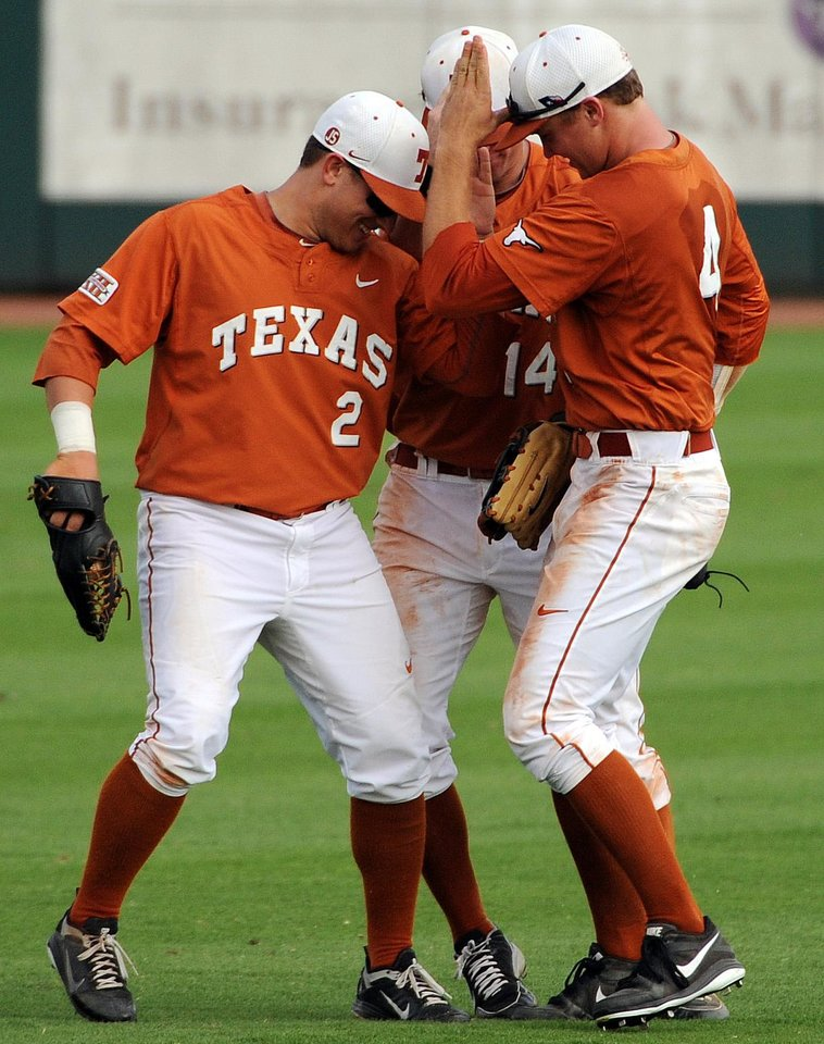 Photo - Texas' Mark Payton, Ben Johnson and Collin Shaw, from left, celebrate the Longhorns' 8-1 victory over Texas A&M in an NCAA college baseball tournament regional game Friday, May 30, 2014, at Reckling Park in Houston. (AP Photo/Houston Chronicle, Eric Christian Smith) MANDATORY CREDIT