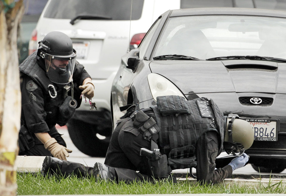 Photo -   Los Angeles Police bomb squad members check for explosive devices outside a Bank of America branch in Los Angeles Wednesday, Sept. 5, 2012. Authorities say two gunmen kidnapped a bank manager, held her overnight and strapped a device to her stomach before robbing a Bank of America. The woman was told by the robbers the device was an explosive. The woman then had employees take money from the bank and put it outside. The suspects remain at large (AP Photo/Damian Dovarganes)