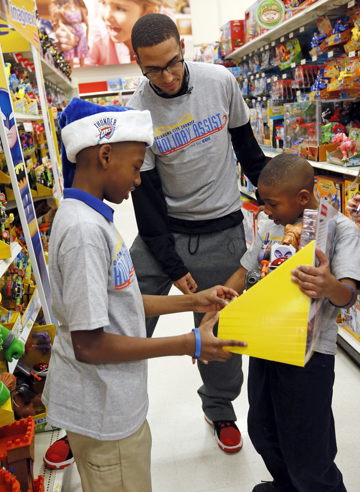 Brothers Ryan Johnson, 11, left, and Ethan Nedio, 6, show Kevin Martin of the Oklahoma City Thunder a toy during the Oklahoma City Thunder's annual Holiday Assist shopping spree at Target, 13924 N Pennsylvania, in Oklahoma City, Monday, Dec. 10, 2012. The ten families who participated in this year's shopping spree are from Sunbeam Family Services' Grandparents Raising Grandchildren program. Photo by Nate Billings, The Oklahoman