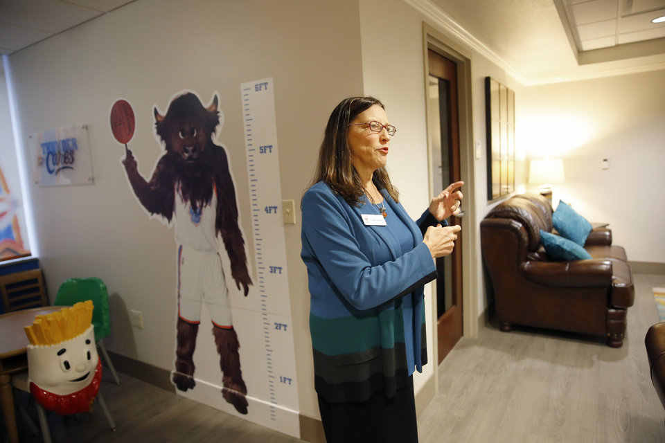 Photo -  Susan Adams talks about the family room at the Ronald McDonald House Garrison Tower on Thursday in Oklahoma City. [Photo by Sarah Phipps, The Oklahoman]