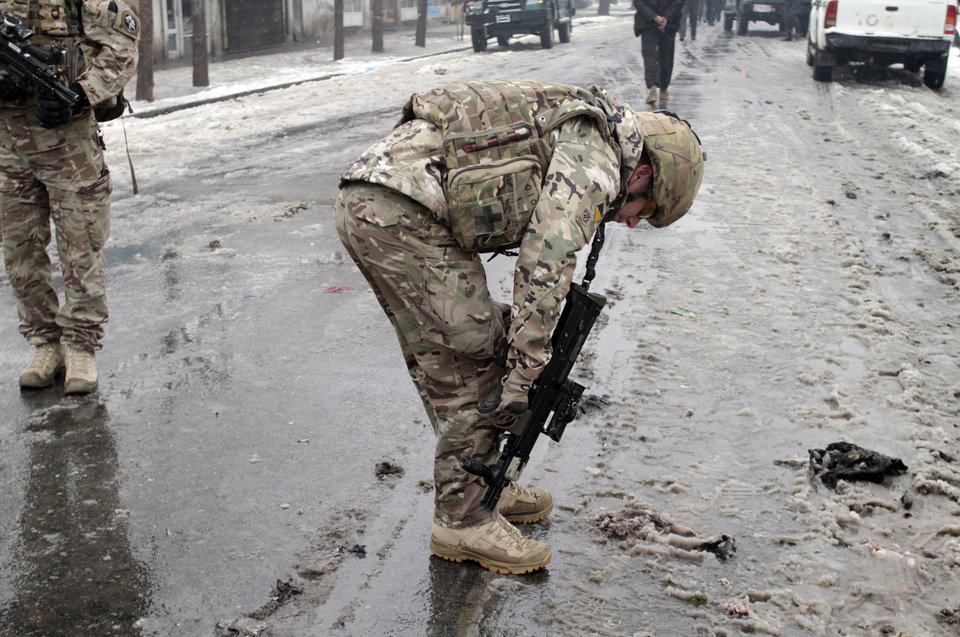 A Britain soldier looks for evidences at the scene of a suicide attack in Kabul, Afghanistan, Wednesday, Feb. 27, 2013. A man wearing a black overcoat and carrying an umbrella as a shelter against the heavy snow crossed a street in the Afghan capital early Wednesday morning toward an idling bus filled with Afghan soldiers, where he laid down and wiggled underneath. Then he exploded, engulfing the undercarriage of the bus in flames. (AP Photo/Musadeq Sadeq)