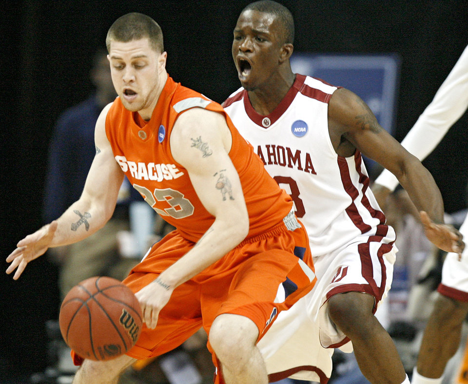 Oklahoma's Willie Warren (13) defends on Syracuse's Eric Devendorf (23) during the first half of the NCAA Men's Basketball Regional at the FedEx Forum on Friday, March 27, 2009, in Memphis, Tenn.