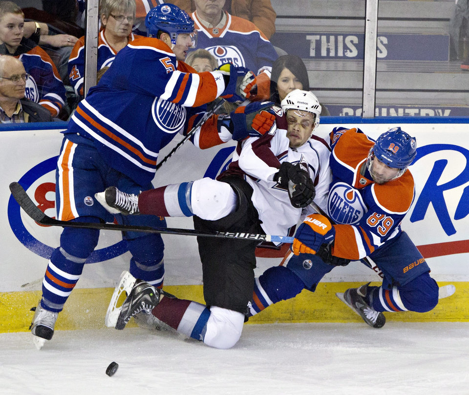 Colorado Avalanche's John Mitchell, center, is checked by Edmonton Oilers' Ladislav Smid, left, as Sam Gagner (89) looks for the puck during the second period of their NHL hockey game, Monday, Jan. 28, 2013, in Edmonton, Alberta. (AP Photo/The Canadian Press, Jason Franson)