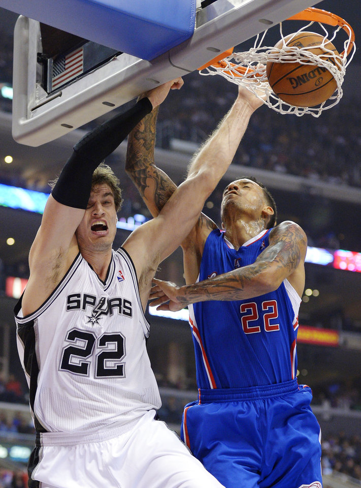 San Antonio Spurs forward Tiago Splitter, left, of Brazil, dunks in front of Los Angeles Clippers forward Matt Barnes during the first half of their NBA basketball game, Wednesday, Nov. 7, 2012, in Los Angeles. (AP Photo/Mark J. Terrill)