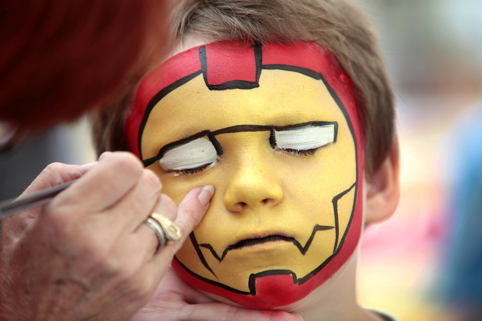 Photo - Kasey Henderson, 6, from Purcell, gets his face painted like Iron Man at the Oklahoma State Fair , Friday, September 13, 2013.  Photo by David McDaniel, The Oklahoman