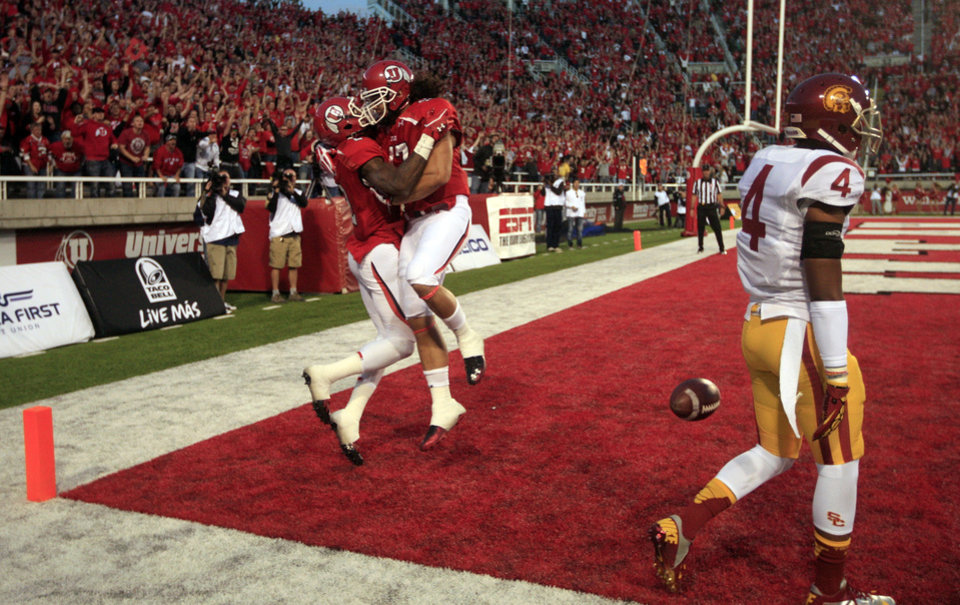 Photo -   Utah wide receiver Kenneth Scott, left, celebrates with teammate David Rolf after scoring while Southern California cornerback Torin Harris (4) walks off the field in the first quarter during an NCAA college football game Thursday, Oct. 4, 2012, in Salt Lake City. (AP Photo/Rick Bowmer)