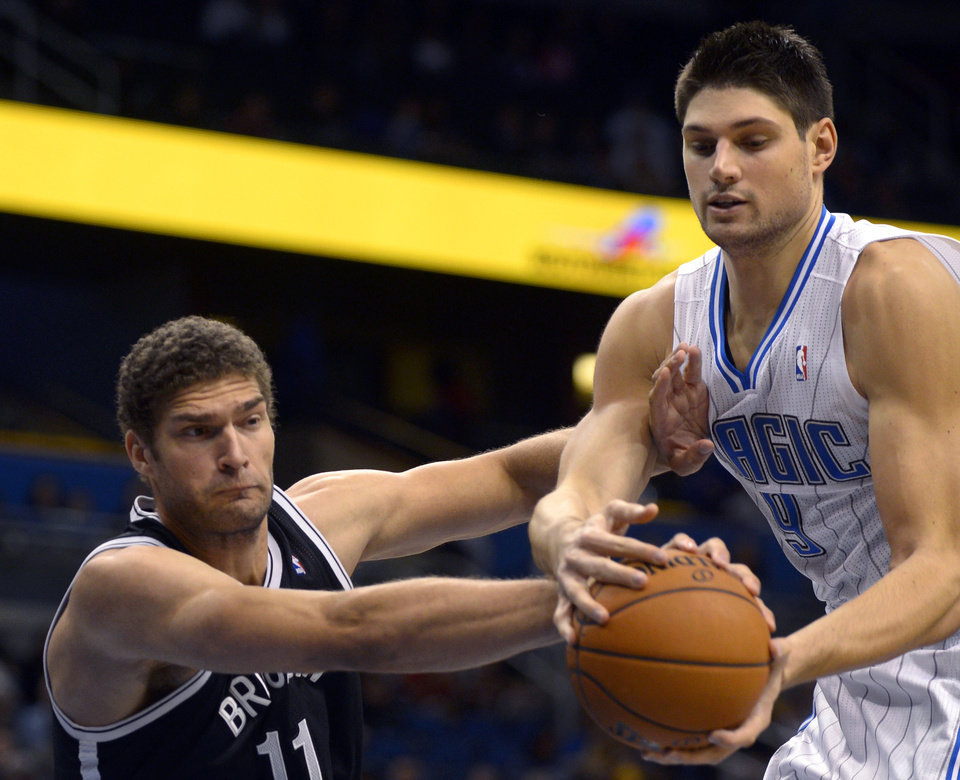Photo -   Brooklyn Nets center Brook Lopez, left, and Orlando Magic center Nikola Vucevic, of Montenegro, battle for a rebound during the first half of an NBA basketball game in Orlando, Fla., Friday, Nov. 9, 2012. (AP Photo/Phelan M. Ebenhack)