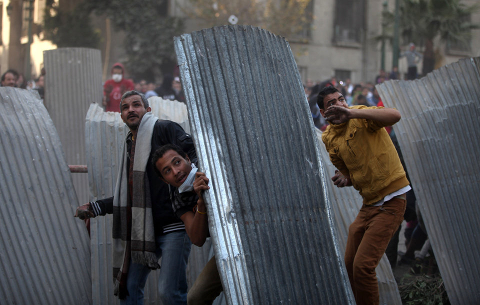 Egyptian protesters take cover as they clash with riot police, not seen, near Tahrir Square, Cairo, Egypt, Friday, Jan. 25, 2013. Two years after Egypt's revolution began, the country's schism was on display Friday as the mainly liberal and secular opposition held rallies saying the goals of the pro-democracy uprising have not been met and denouncing Islamist President Mohammed Morsi. With the anniversary, Egypt is definitively in the new phase of its upheaval. (AP Photo/Khalil Hamra) ORG XMIT: KH129