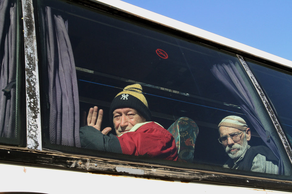 Photo - Men sitting on a bus pose for a photograph as they evacuate the battleground city of Homs, Syria, Friday, Feb. 7, 2014. Children, elderly women on wheelchairs and other civilians were evacuated Friday from besieged neighborhoods of Syria's battleground city of Homs under a deal struck between the government and the opposition that also included a three-day cease-fire allowing aid convoys to enter. (AP Photo)