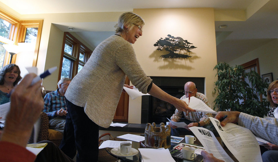 Photo -   In this photo taken Tuesday, Oct. 23, 2012, Cindy Franklin hands out information about how to write letters against a proposed coal exporting facility, in her home in Bellingham, Wash. The progressive college town of Bellingham is at the center of one of the fiercest environmental debates in the region: should the Northwest become a hub for exporting U.S. coal to Asia? A proposal to build one of as many as five coal terminals here has divided the town, pitting union and businesses that welcome jobs against environmentalists who worry about coal dust and greenhouse gas emissions. A trade group is running TV ads touting the projects, while numerous cities such as Seattle and Portland are opposing coal trains through their communities. (AP Photo/Elaine Thompson)