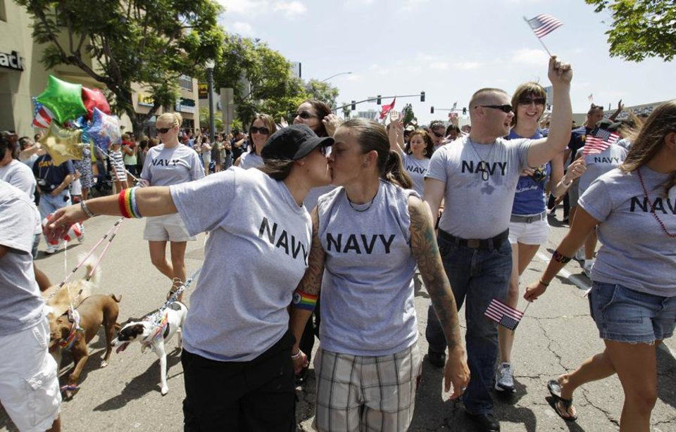 Two women, both active duty sailors in the Navy who gave their names as Nikki, left, and Lisa, kiss as they march in the Gay Pride Parade in San Diego Saturday, July 16, 2011. More than 200 active duty troops and war veterans waving small American flags alongside rainbow banners marched in San Diego's gay pride parade in what is believed to be the first time an identifiable group of active duty troops has participated in such an event in the U.S. (AP Photo/Gregory Bull)