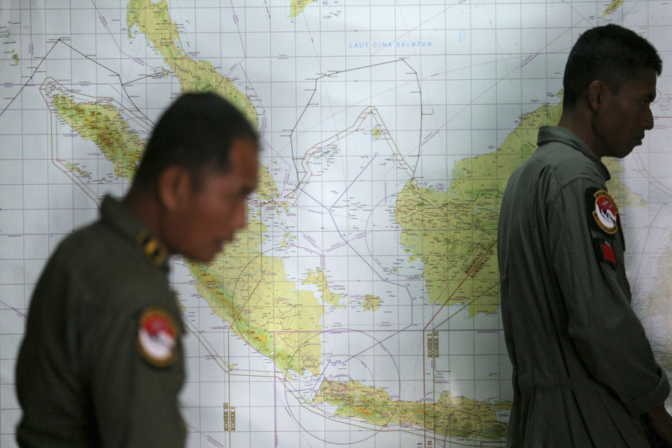 Photo - Indonesian Air Force officers stand against a map that shows a part of the South China Sea during a briefing following a search operation for the missing Malaysia Airlines Boeing 777, at Suwondo air base in Medan, North Sumatra, Indonesia, Thursday, March 13, 2014. The hunt for the missing jetliner has been punctuated by false leads since it disappeared with 239 people aboard about an hour after leaving Kuala Lumpur for Beijing early Saturday. (AP Photo/Binsar Bakkara)