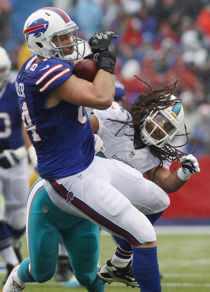 Photo - Buffalo Bills tight end Scott Chandler (84) makes a catch as he is hit by Miami Dolphins outside linebacker Philip Wheeler (52) during the first half of an NFL football game Sunday, Dec. 22, 2013, in Orchard Park, N.Y. (AP Photo/Bill Wippert)