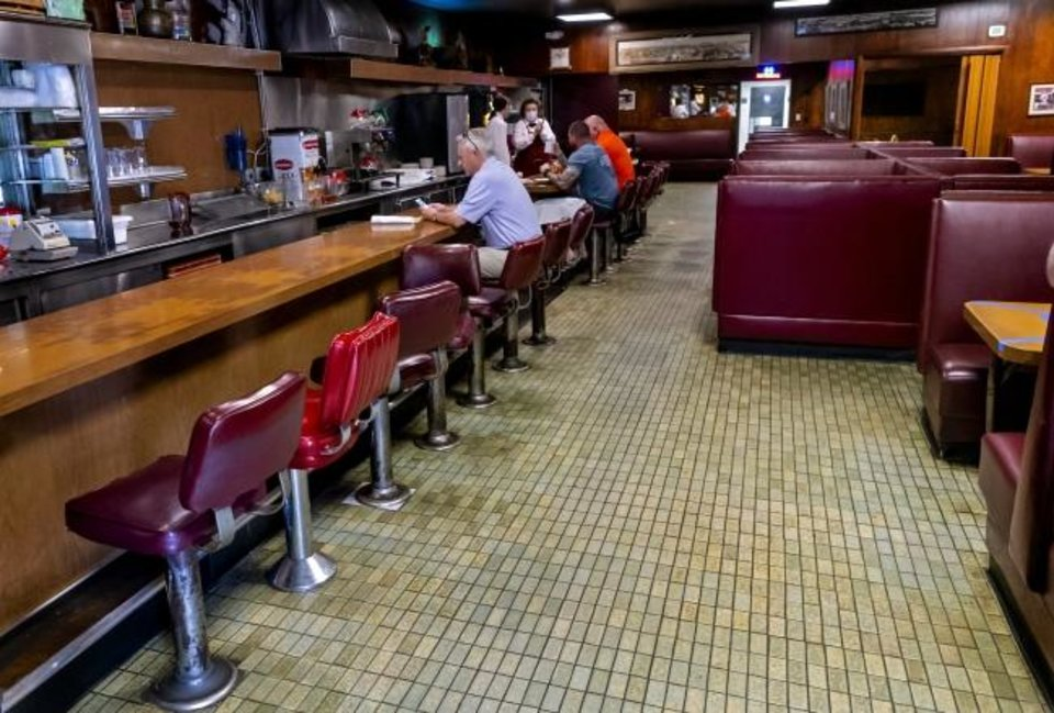 Photo -  Customers sit for lunch Friday at a reopened Cattlemen's Steakhouse in Oklahoma City. Only about 30 customers ate lunch inside the restaurant, which usually is bustling with patrons. [Chris Landsberger/The Oklahoman]