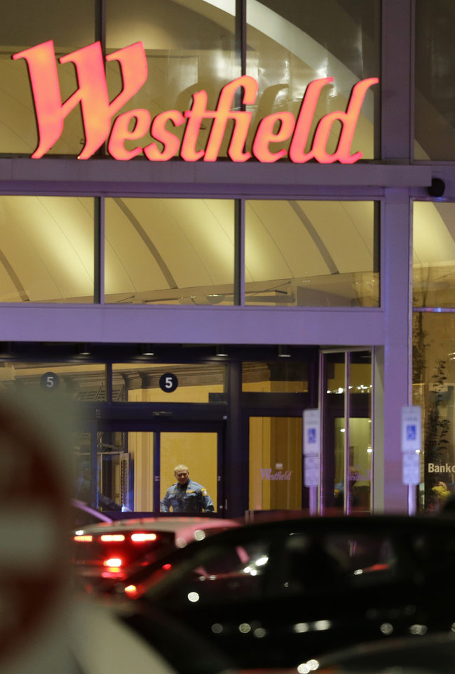 Photo - An official stands at an entrance to the Garden State Mall following reports of a shooter, Monday, Nov. 4, 2013, in Paramus, N.J. Hundreds of law enforcement officers converged on the mall Monday night after witnesses said multiple shots were fired there. (AP Photo/Julio Cortez)