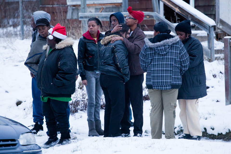 Friends and family members console each other, Tuesday, Dec. 25, 2012 in Flint, Mich. Michigan authorities say five people are dead in two separate incidents of what is believed to be accidental carbon monoxide poisoning. (AP Photo/Flint Journal, Griffin Moores)
