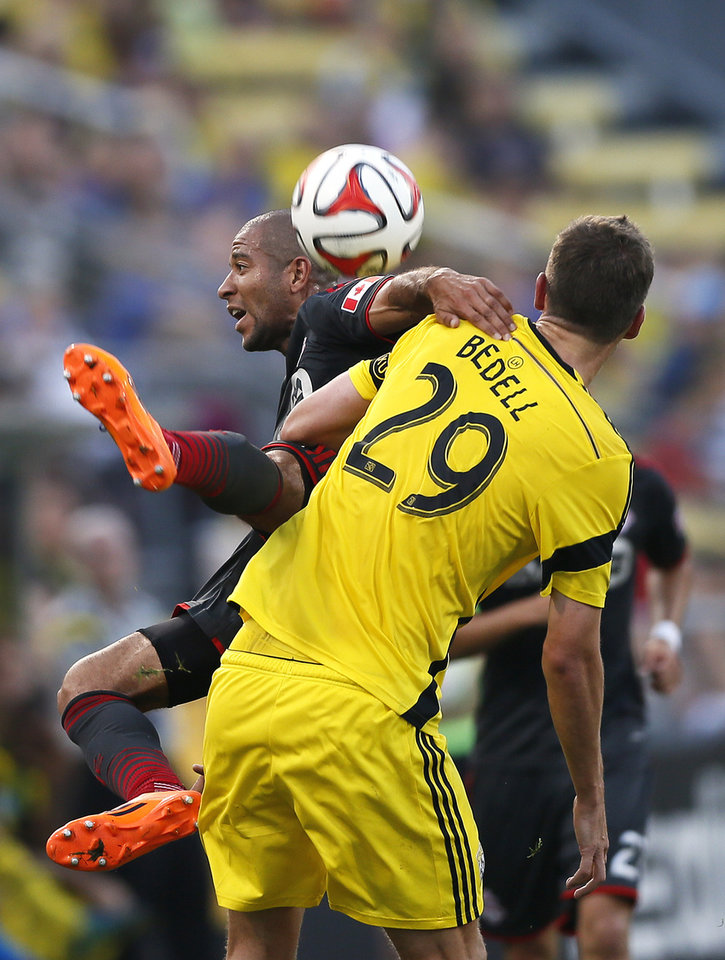 Photo - Toronto FC defender Justin Morrow, rear, falls to the ground after going for a header against Columbus Crew forward Adam Bedell (29) in the first half of an MLS soccer game Saturday, Aug. 9, 2014, in Columbus, Ohio (AP Photo/The Columbus Dispatch, Eamon Queeney)