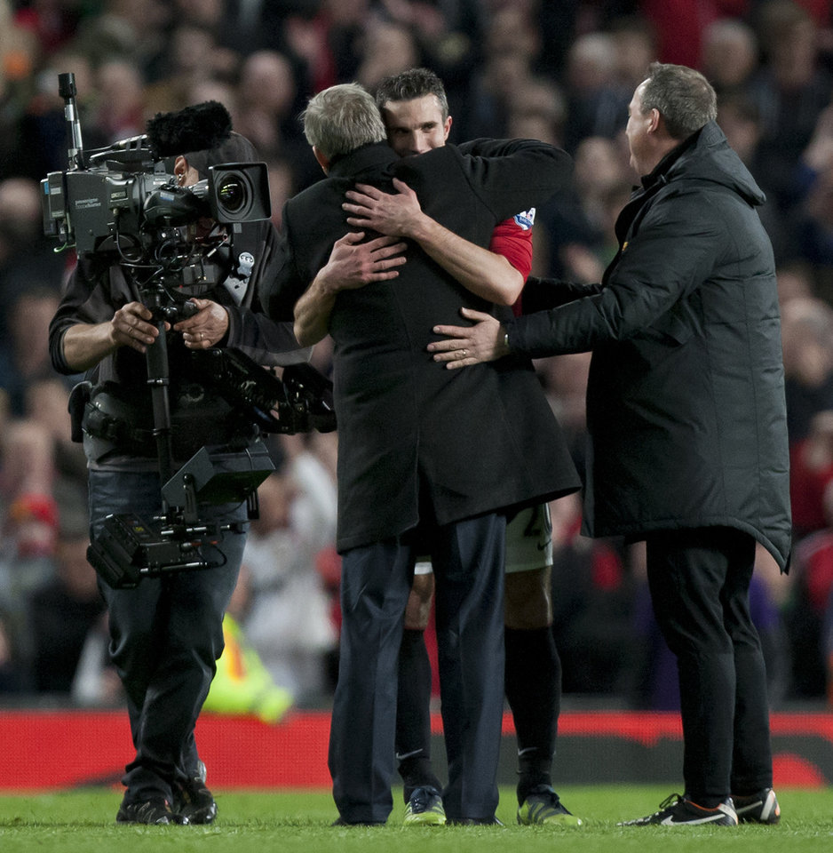 Photo - Manchester United's Robin van Persie, centre right embraces team manager Sir Alex Ferguson celebrating as their team wins their 20th English Premier League title after their 3-0 win over Aston Villa in their soccer match at Old Trafford Stadium, Manchester, England, Monday April 22, 2013. (AP Photo/Jon Super)