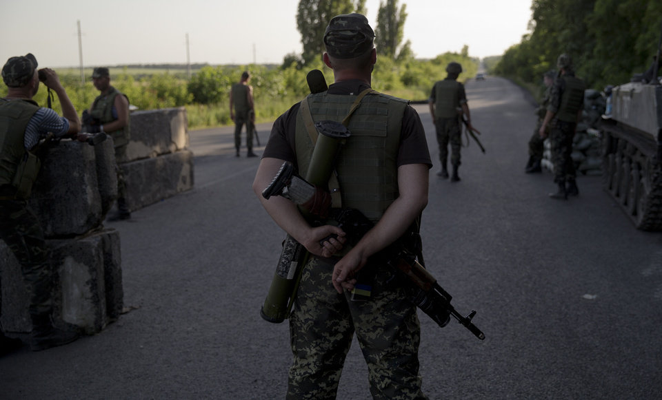 Photo - Ukrainian soldiers man a checkpoint outside the town of Amvrosiivka, eastern Ukraine, close to the Russian border, Thursday, June 5, 2014. The Ukrainian military was on alert on its eastern border with Russia on Thursday amid reports that separatist forces launched attacks on a border crossing near the village of Marinyvka.(AP Photo/Vadim Ghirda)