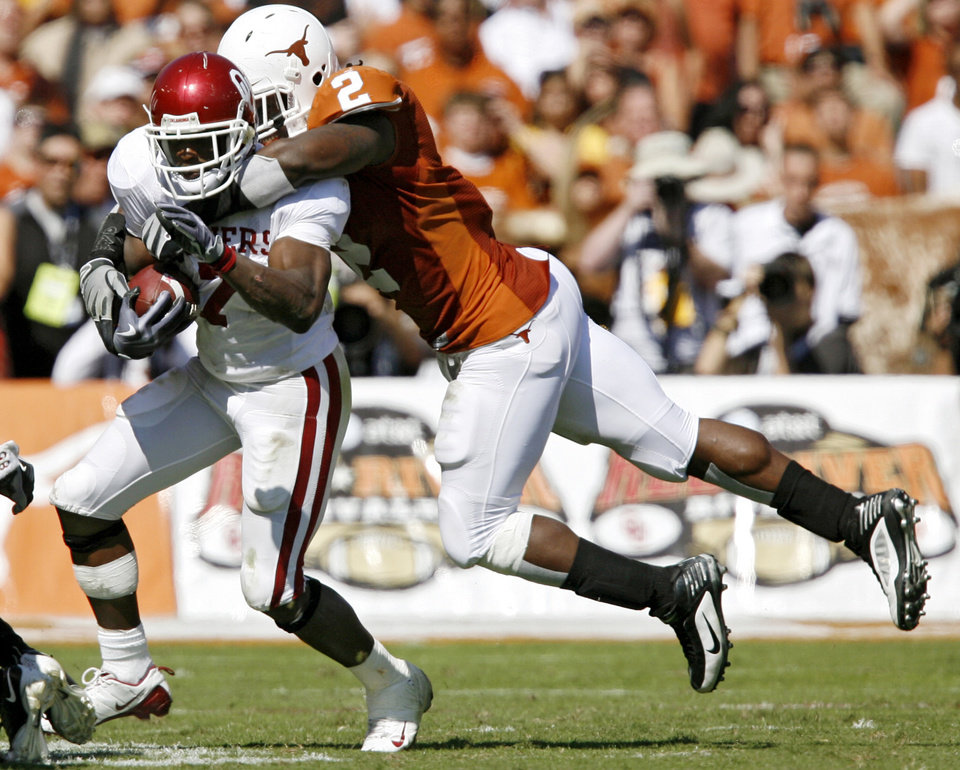 Photo - Oklahoma's DeMarco Murray (7) carries Texas' Sergio Kindle (2) while taking the ball up field during the Red River Rivalry college football game between the University of Oklahoma Sooners (OU) and the University of Texas Longhorns (UT) at the Cotton Bowl in Dallas, Texas, Saturday, Oct. 17, 2009. Photo by Chris Landsberger, The Oklahoman