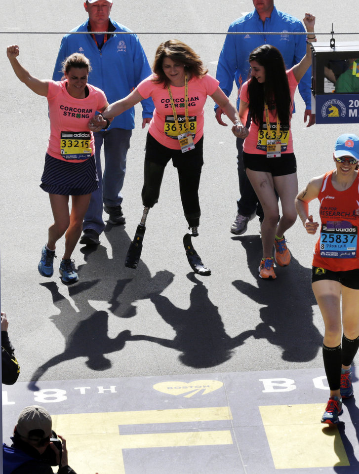 Photo - Double amputee Celeste Corcoran, center, a victim of last year's bombings, reaches the finish line of the 118th Boston Marathon, Monday, April 21, 2014, in Boston, with the aid her sister Carmen Acabbo, left, and daughter Sydney, right, who was also wounded last year. (AP Photo/Charles Krupa)