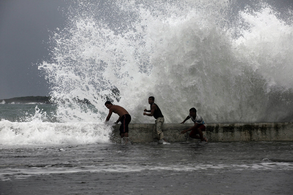 Photo -   Men stand behind the seawall as waves brought by Tropical Storm Isaac splash over them in Baracoa, Cuba, Saturday, Aug. 25, 2012. Tropical Storm Isaac pushed into Cuba on Saturday after sweeping across Haiti's southern peninsula. Isaac's center made landfall just before midday near the far-eastern tip of Cuba. (AP Photo/Ramon Espinosa)