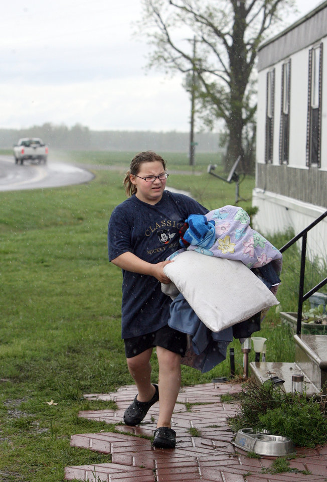 Photo - Daphne Warren carries bedding out of her parents home near Wolf Island, Mo. after an evacuation order was issued for people living in Mississippi County who would be flooded out if the U.S. Army Corps of Engineers dynamites a levee on the Mississippi River on Wednesday, April 27, 2011.    More rain fell Wednesday, creating new worries as many rivers neared their crest. For much of southern Missouri, it was at least the sixth straight day of rain, and some parts of the region have received 15 inches in that time, said Mary Lamm, a National Weather Service hydrologist. (AP Photo/St. Louis Post-Dispatch, David Carson)