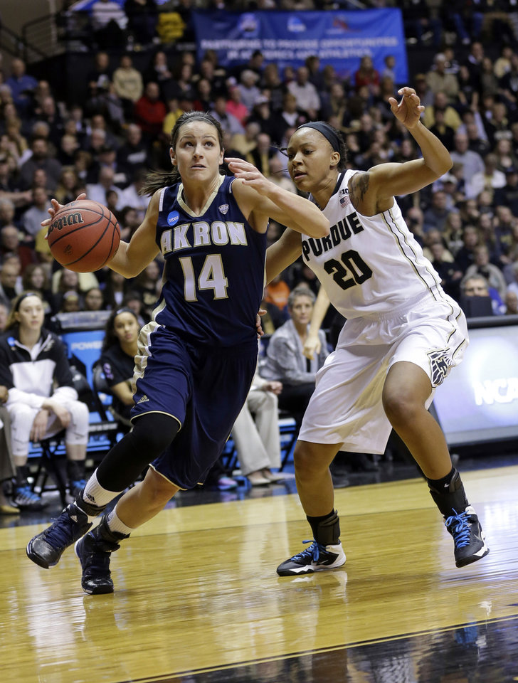 Photo - Akron guard Hanna Luburgh, left, drives on Purdue guard Dee Dee Williams during the first half of a first-round game in the NCAA women's college basketball tournament, Saturday, March 22, 2014, in West Lafayette, Ind. (AP Photo/Michael Conroy)