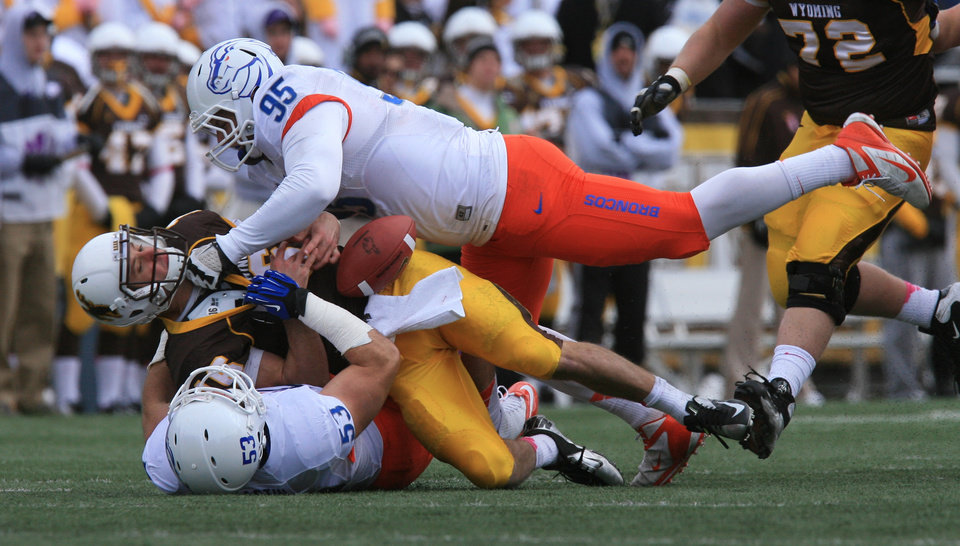 Photo -   Boise State's Darren Koontz (95) top, and Beau Martin (53), bottom, sack Wyoming quarterback Brett Smith causing a fumble in the second half of an NCAA college football game, Saturday, Oct. 27, 2012 at War Memorial Stadium in Laramie, Wyo. Boise State won 45-14. (AP Photo/The Idaho Statesman, Chris Butler) LOCAL TV OUT (KTVB 7) MANDATORY CREDIT