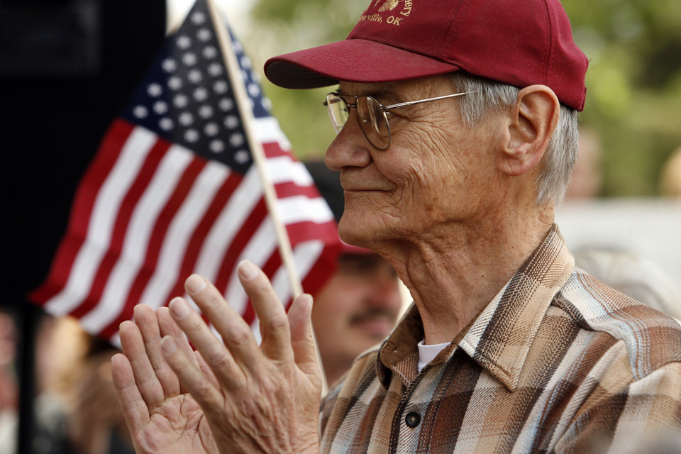 Photo - Larry Iovan of Slaughterville applauds as citizens hold a Tax Day Tea Party at the Santa Fe Station in Norman, Okla. on Wednesday, April 15, 2009.  