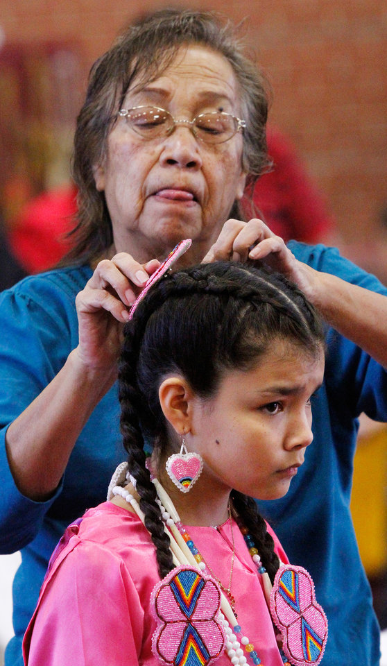 Francelina Roy, a Kiowa,  places a colorful headpiece into the hair of her granddaughter, Stephanie Tongkeamha, 10, who is Ponca and Kiowa.  She performed cloth dances with a sister and a cousin.  At least 500 people representing several dozen Native American Nations within the state attended  a New Year's pow-wow in the Centennial Building at State Fair Park Saturday , January 7, 2012,   The celebration started around shortly after noon and continued into the night.   Several hundred took part in the various dancers and the dancers wore tribal regalia.  Photo by Jim Beckel, The Oklahoman