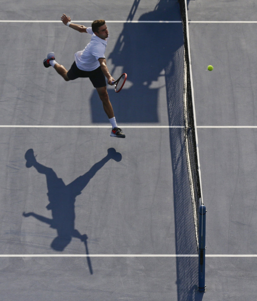 Photo - Marin Cilic, of Croatia, returns a shot at the net against Gilles Simon, of France, during the fourth round of the 2014 U.S. Open tennis tournament, Tuesday, Sept. 2, 2014, in New York. (AP Photo/Charles Krupa)