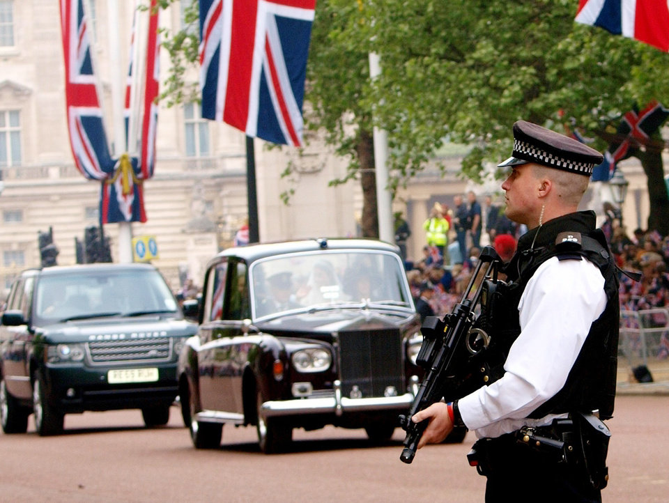 Photo - An armed British policeman stands guard as Kate Middleton is driven along the Mall on her way to her wedding with Britain's Prince William at London's Westminster Abbey, Friday April 29, 2011.(AP Photo/Max Nash, pool) ORG XMIT: RWAT114