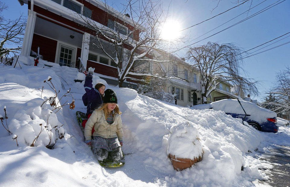 Holly Stout, 8, left, and Anna Roth, 7, slide down icy steps in Maplewood, N.J., Saturday, Feb. 9, 2013. The Northeast storm dumped over a foot of snow in northern N.J. (AP Photo/Rich Schultz) ORG XMIT: NJRS102