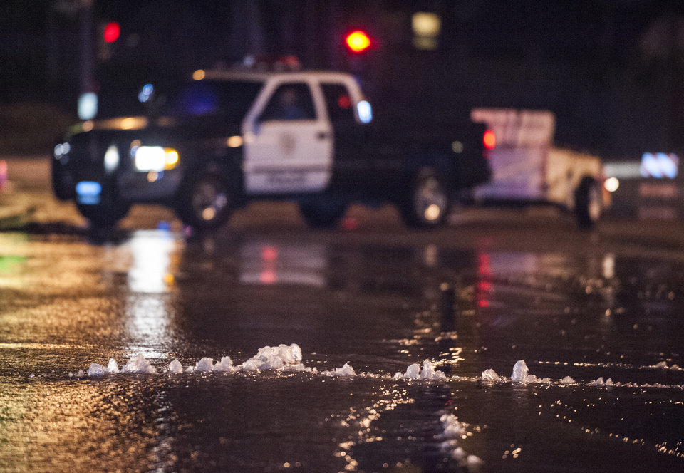 Photo - Water bubbles up through the pavement along Gilbert Street just south of Rosecrans in Fullerton Friday night March 28, 2014 following an 5.1 earthquake. Police closed off the street as crews placed cones around the area. (AP Photo/The Orange County Register, Mark Rightmire)