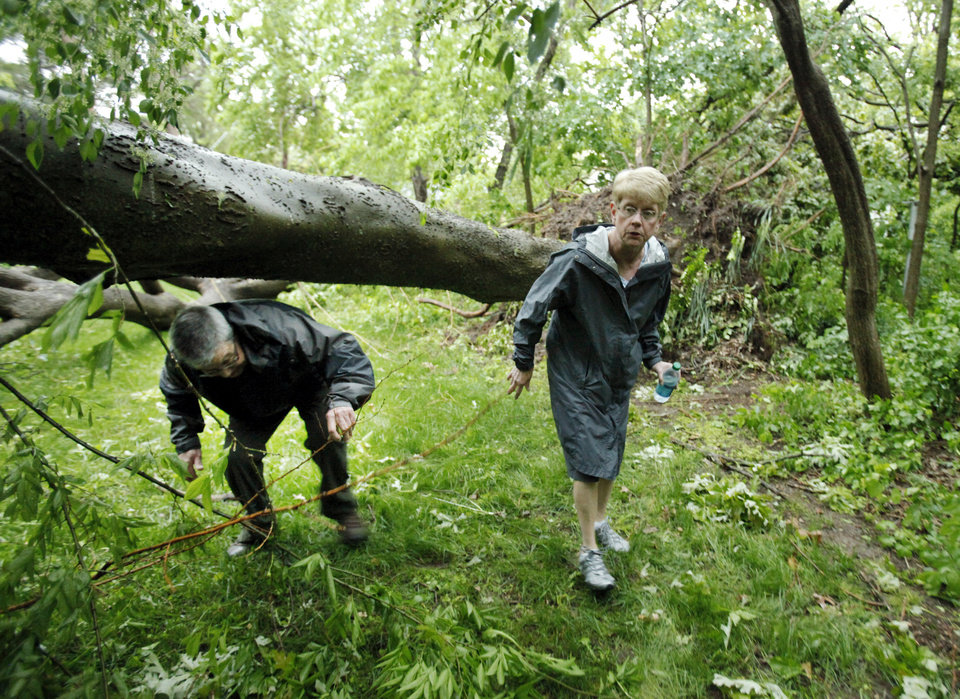 Dennis Frank and wife Jill Kendall maneuver through their back yard on Camden Way after a reported tornado that struck the west and central pars of town on Friday, April 13, 2012, in Norman, Okla.  Photo by Steve Sisney, The Oklahoman