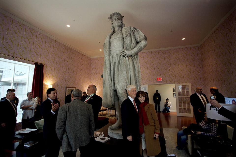 "Leaders of the Italian-American community, civil servants from New York and Italy, including police and sanitation workers and other guests, stand in what is known as the living room created by artist Tatzu Nishi that surrounds Gaetano Russo's 1892 sculpture of Christopher Columbus 75 Feet Above Columbus Circle Sunday, Oct. 7, 2012, in New York. The art installation �Tatzu Nishi: Discovering Columbus,"" which brings people to eye level with the Columbus statue, became part of an annual wreath laying ceremony that celebrates Columbus Day. Posing center right for a photograph is Mario Gabelli, Grand Marshall of the 2012 Columbus Day parade, and Natalia Quintavalle, Consul General of Italy in New York. (AP Photo/Craig Ruttle)"