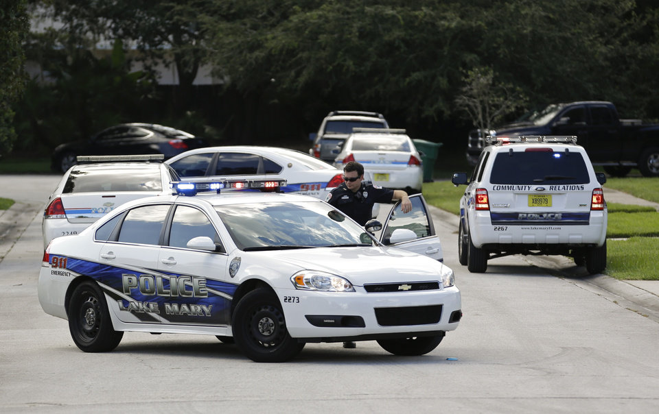 Photo - Police cars block the street at the scene of a domestic incident in the Lake Mary, Fla. neighborhood where George Zimmerman and his wife Shellie had lived during his murder trial, Monday, Sept. 9, 2013. Zimmerman's wife says on a 911 call that her estranged husband punched her father in the nose, grabbed an iPad out of her hand and smashed it and threatened them both with a gun. Zimmerman was recently found not guilty for the 2012 shooting death of Trayvon Martin. (AP Photo/John Raoux)