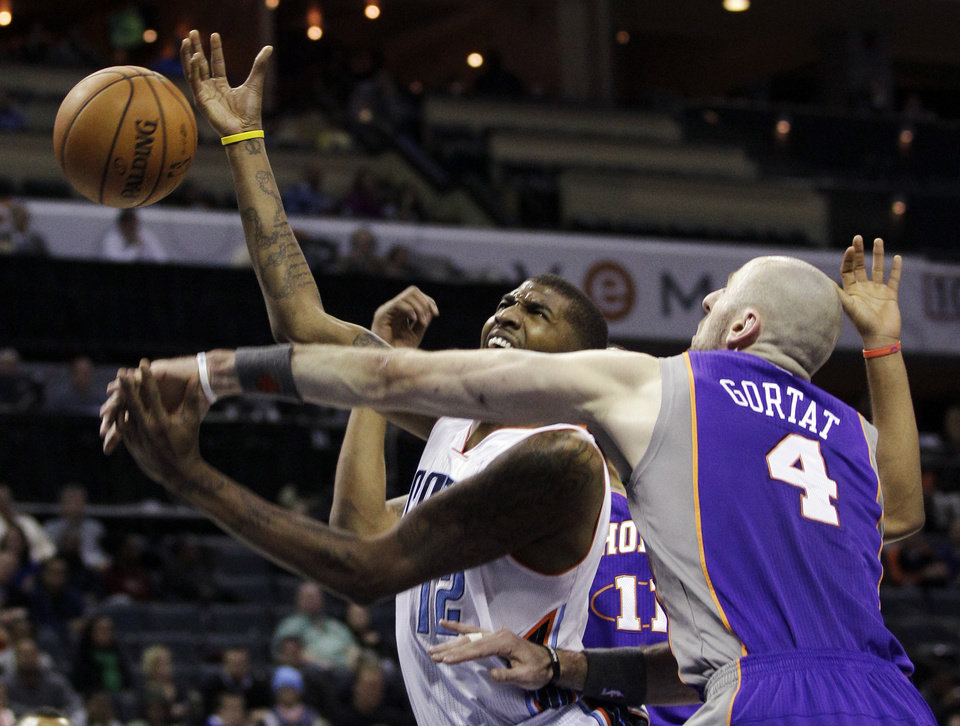 Charlotte Bobcats' Tyrus Thomas (12) is fouled by Phoenix Suns' Marcin Gortat (4) during the first half of an NBA basketball game in Charlotte, N.C., Wednesday, Nov. 7, 2012. (AP Photo/Chuck Burton)