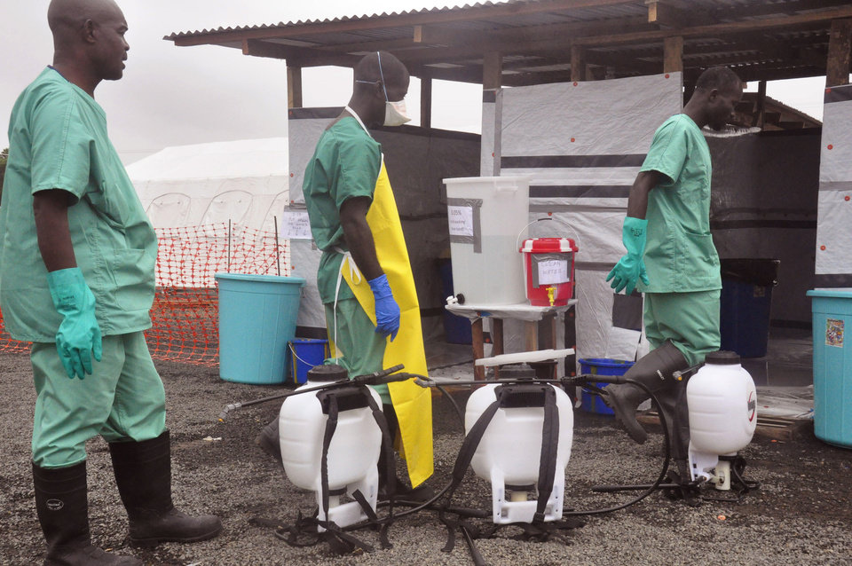 Photo - Health workers prepare disinfectant in containers, foreground,  to spray at an Ebola treatment center in the city of Monrovia, Liberia, Monday, Aug. 18, 2014. Liberia's armed forces were given orders to shoot people trying to illegally cross the border from neighboring Sierra Leone, which was closed to stem the spread of Ebola, local newspaper Daily Observer reported Monday. (AP Photo/Abbas Dulleh)