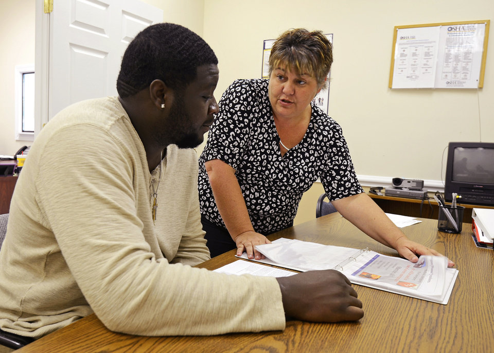 In this May 19, 2014 photo, Micki Taylor, branch manager of the Mega Force Staffing Services in Kinston, N.C., reviews an orientation booklet with Kenneth Wilson, who is training to become a forklift operator, in Kinston, N.C. Payroll processer ADP said Wednesday, July 2, 2014, that private employers added 281,000 jobs last month, up from 179,000 in the previous month. (AP Photo/Kinston Free Press, Sara Pezzoni)