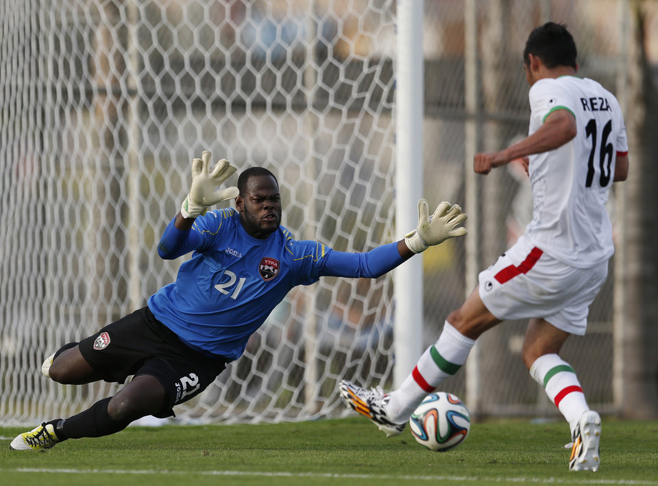Photo - Trinidad and Tobago's national soccer team goalkeeper Jan Michael Williams, left, defends against Iran's Reza Ghouchannejad during the second half of an international soccer friendly at the Corinthians soccer team training center Sao Paulo, Brazil, on Sunday, June 8, 2014. Iran will play in group F of the 2014 soccer World Cup. (AP Photo/Julio Cortez)