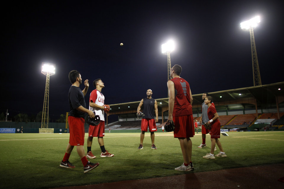 In this photo taken Dec. 29, 2012, baseball players warm up prior to a game in Caguas, Puerto Rico. On an island where the name of Roberto Clemente is emblazoned on stadiums, streets and schools, the sport of baseball is poised to make a late-inning rally. In the past year, Major League Baseball reported the second-highest number of signings from Puerto Rico since the year 2000. (AP Photo/Ricardo Arduengo)