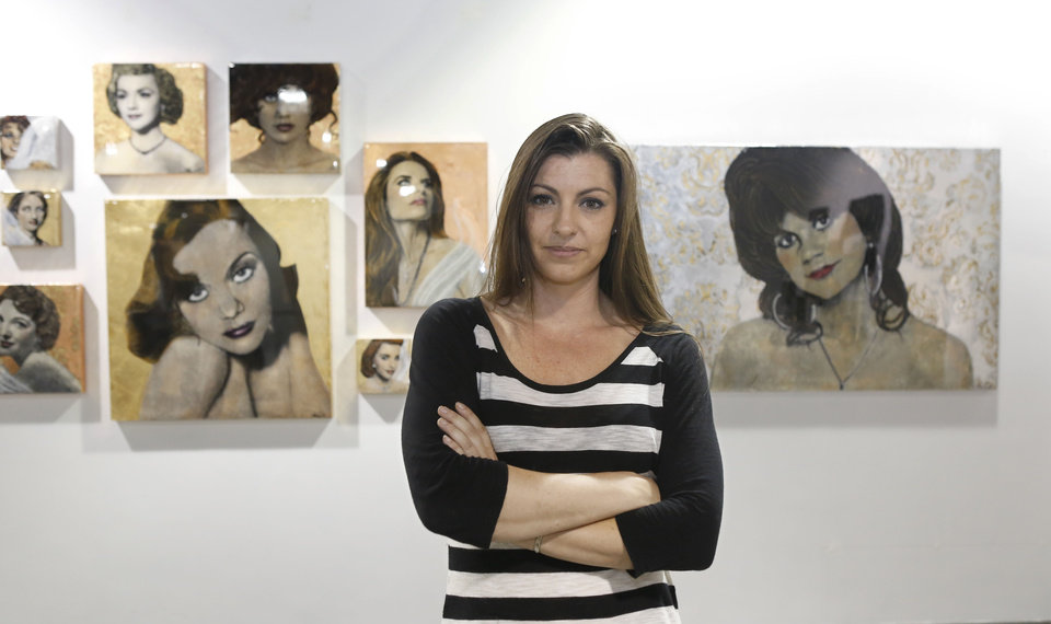 Photo - In this photo taken Monday, June 24, 2013, artist Maren Conrad poses by her exhibit of women with sexual ties to California Governors, in Sacramento, Calif.   The show, titled